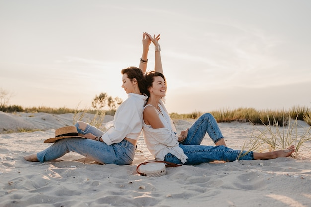 Dwie młode koleżanki bawią się na plaży o zachodzie słońca, homoseksualne lesbijki kochają romans
