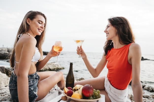 Dwie młode koleżanki na pikniku na plaży piją koktajle