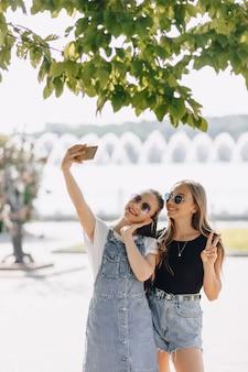 Dwie młode ładne dziewczyny na spacerze w parku robią sobie zdjęcia przez telefon. w słoneczny letni dzień radość i przyjaźnie.