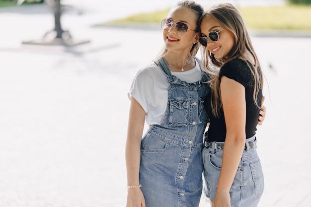 Dwie młode ładne dziewczyny na spacerze w parku. słoneczny letni dzień, radość i przyjaźnie.