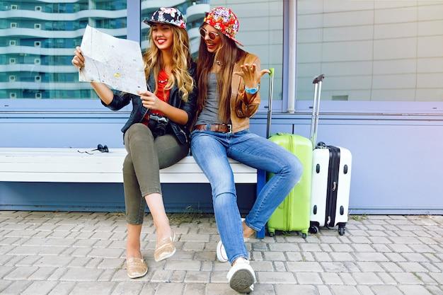 Dwie młode ładne dziewczyny odkrywają i patrzą na mapę przed podróżą, uśmiechają się i bawią przed nowymi emocjami. najlepszy przyjaciel pozuje z bagażem.