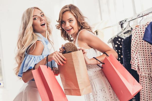 Dwie młode ładne dziewczyny oglądające sukienki i przymierzające je, wybierając w sklepie