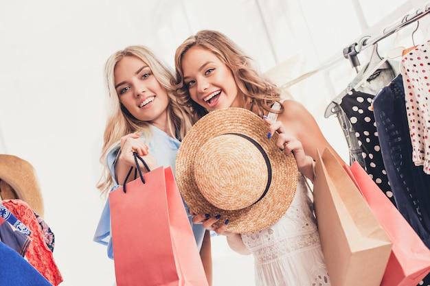 Dwie młode ładne dziewczyny patrzą na sukienki i przymierzają je wybierając w sklepie