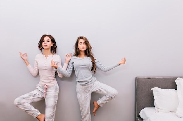 Dwie młode ładne dziewczyny w nocnej piżamie na szarej ścianie. robią medytację z zamkniętymi oczami.