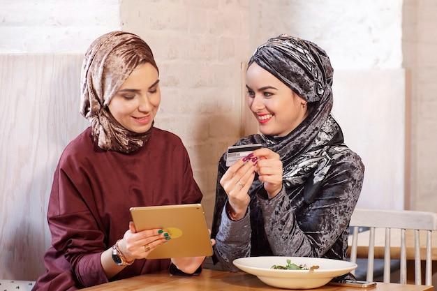 Dwie młode ładne muzułmanki rozmawiają i robią zakupy online za pomocą elektronicznego tabletu