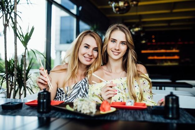 Dwie młode, ładne siostry blondynki bawią się sushi w nowoczesnej kawiarni, spędzają razem czas