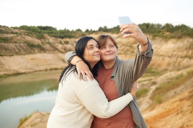 Dwie młode lesbijki obejmując się nawzajem i robiąc selfie portret na telefonie komórkowym na tle pięknego jeziora na zewnątrz