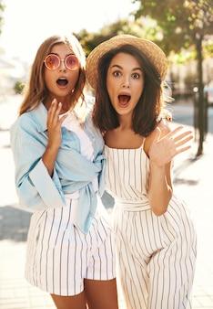 Dwie młode modelki brunetki i blondynki pozujące na ulicy