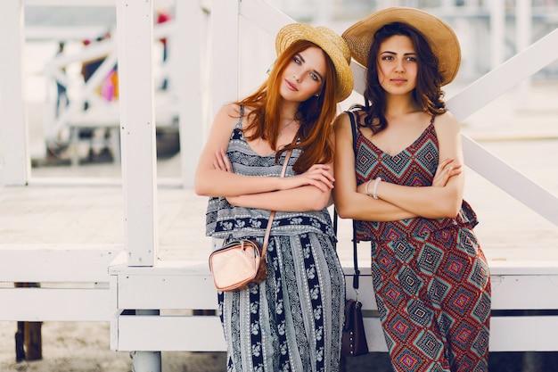 Dwie młode modne kobiety w słomkowym kapeluszu i stylowym letnim stroju pozują w pobliżu tropikalnego baru na plaży