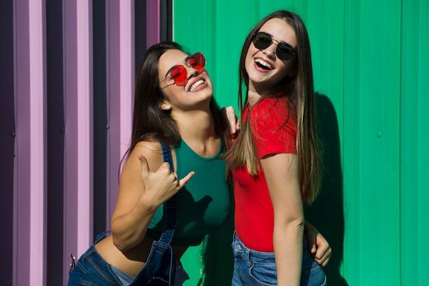 Dwie młode najlepsze koleżanki stojące przy ścianie