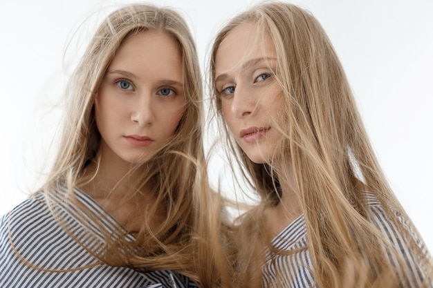 Dwie młode nastoletnie ładne kaukaskie bliźniaczki w pasiastych koszulach z długimi włosami