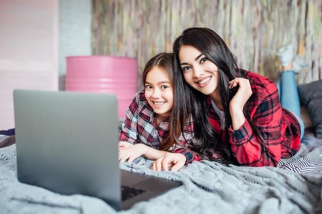 Dwie młode nastoletnie siostry używają laptopa do wspólnego oglądania filmów w domu w sypialni