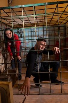 Dwie młode ofiary uwięzione w metalowej klatce z zakrwawioną ścianą za nimi, chłopiec wyciągający rękę przez kraty i próbujący się wydostać