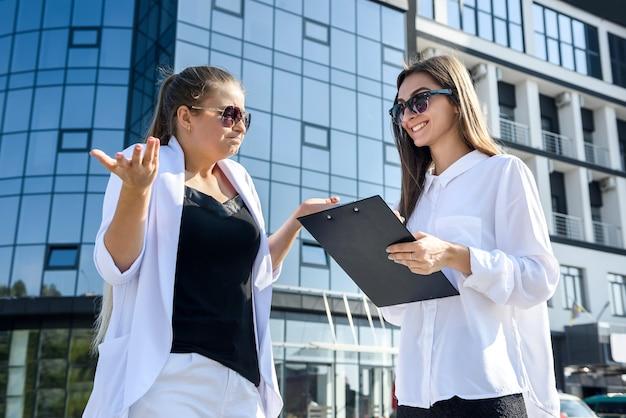 Dwie młode panie biznesu negocjują w pobliżu centrum biznesowego