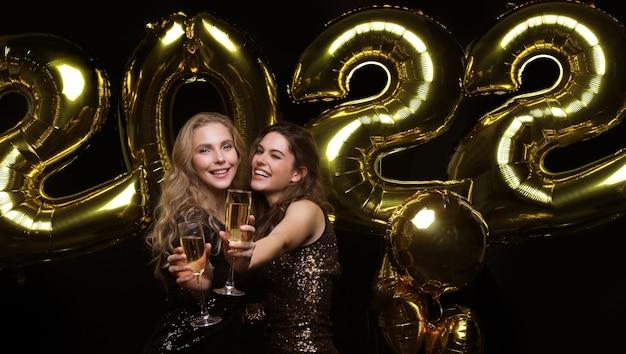 Dwie młode panie piją szampana. obraz dziewcząt z balonami na białym tle na czarnym tle, bawiących się na imprezie wigilijnej lub sylwestrowej 2022.