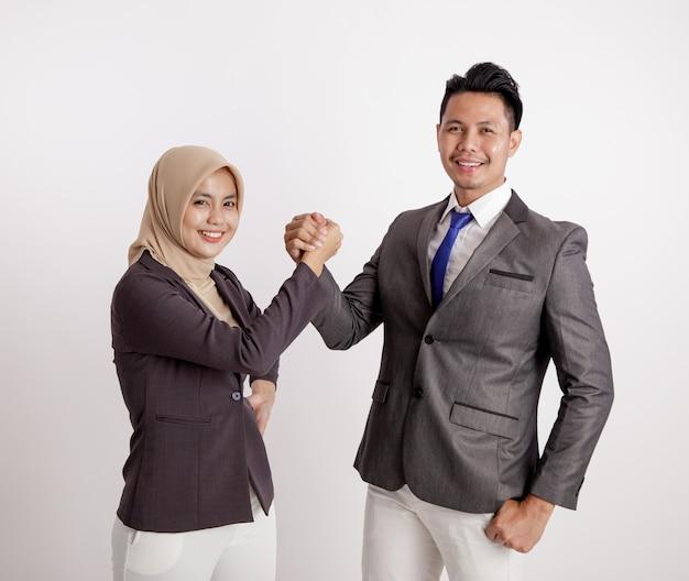 Dwie młode pary biznesowe bardzo podekscytowany pracy patrząc na aparat trzymając rękę razem na białym tle