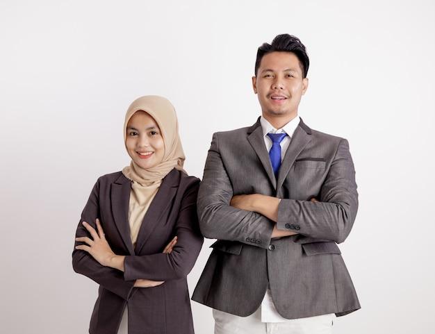 Dwie młode pary biznesowe uśmiechnięte skrzyżowane ramiona patrząc na kamery na białym tle
