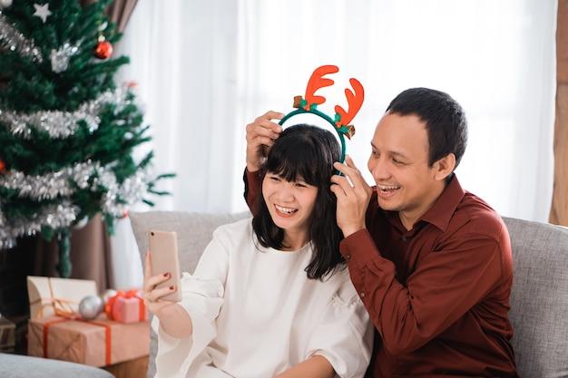 Dwie młode pary robi rozmowę wideo i robi głupią minę za pomocą smartfona w domu