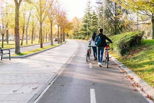 Dwie młode pary spacerujące ścieżką rowerową ze wspólnym elektrycznym rowerem elektrycznym w dłoniach w pięknym parku z wieloma drzewami o zachodzie słońca