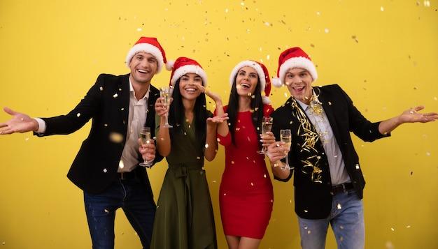 Dwie młode pary w świątecznych kapeluszach urządzają przyjęcie sylwestrowe, śmiejąc się z radości, wiwatując kieliszkami szampana i rzucając jaskrawe konfetti