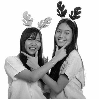 Dwie młode piękne azjatyckie nastolatki razem na białym tle. czarno-białe zdjęcie