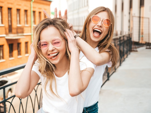 Dwie młode piękne blond uśmiechnięte dziewczyny hipster w modne letnie białe ubrania. .pozytywne modele zabawy w okularach przeciwsłonecznych. używając palców jak uszy królika