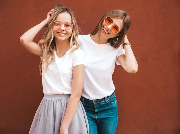 Dwie młode piękne blond uśmiechnięte dziewczyny hipster w modne letnie białe ubrania t-shirt. kobiety pozuje w ulicznej pobliskiej czerwieni ścianie. pozytywne modele zabawy w okularach przeciwsłonecznych
