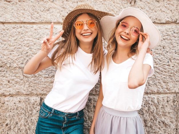 Dwie młode piękne blond uśmiechnięte dziewczyny hipster w modne letnie białe ubrania t-shirt. kobiety pozuje w ulicznej pobliskiej ścianie.