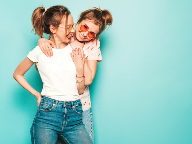 Dwie młode piękne blond uśmiechnięte dziewczyny hipster w modne letnie hipster jeans ubrania. seksowne beztroskie kobiety pozuje blisko błękit ściany. modne i pozytywne modele zabawy