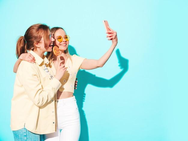 Dwie młode piękne blond uśmiechnięte hipsterki w modnych letnich ubraniach
