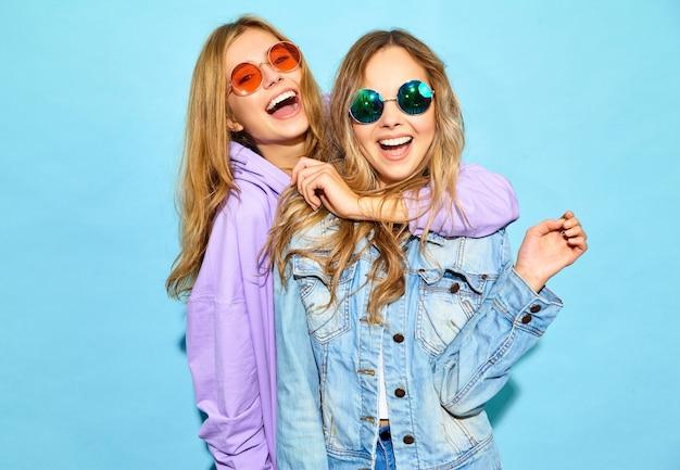 Dwie młode piękne blond uśmiechnięte kobiety hipster w modne letnie ubrania. seksowne beztroskie kobiety pozuje blisko błękit ściany w okularach przeciwsłonecznych. pozytywne modele oszalały
