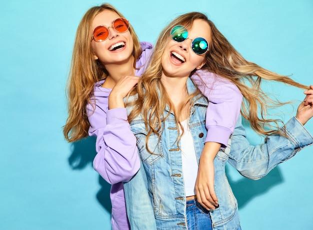 Dwie młode piękne blond uśmiechnięte kobiety hipster w modne letnie ubrania. seksowne beztroskie kobiety pozuje blisko błękit ściany w okularach przeciwsłonecznych. pozytywne modele