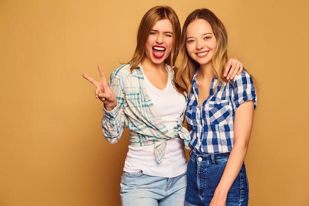 Dwie młode piękne blond uśmiechnięte w modne letnie koszule w kratkę