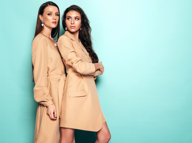 Dwie młode piękne brunetki w ładne modne lato podobne garnitury ubrania. seksowne beztroskie kobiety pozowanie w pobliżu niebieską ścianą w studio