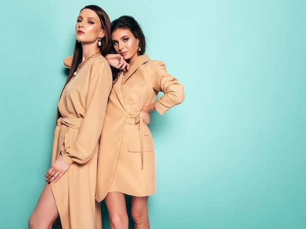 Dwie młode piękne brunetki w ładne modne letnie ubrania. seksowne beztroskie kobiety pozowanie w pobliżu niebieską ścianą w studio. kobiety przytulić się