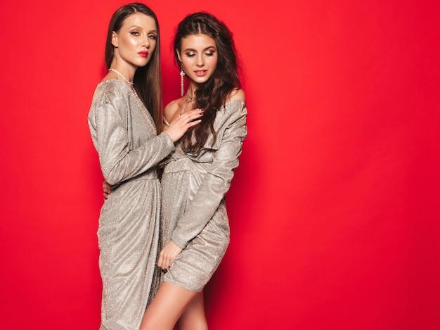 Dwie młode piękne brunetki w ładnej modnej letniej błyszczącej sukience