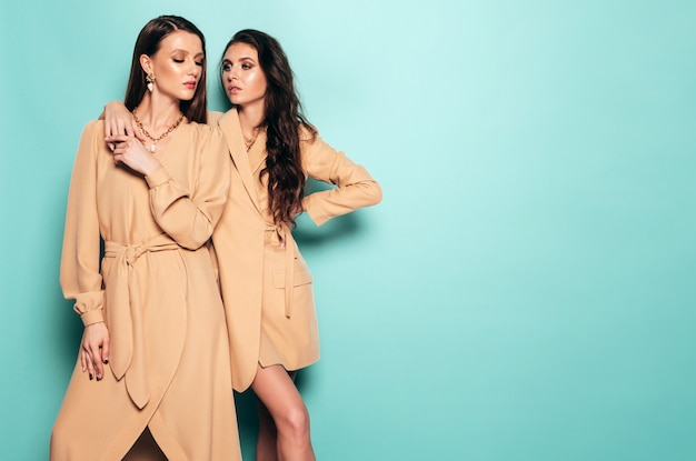 Dwie młode piękne dziewczyny brunetka w ładne modne letnie ubrania. seksowne beztroskie kobiety pozuje blisko błękit ściany w studiu