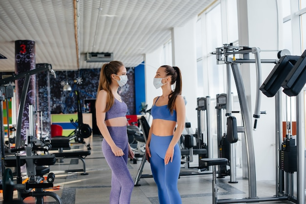 Dwie młode piękne dziewczyny ćwiczą na siłowni w maskach podczas pandemii