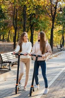 Dwie młode piękne dziewczyny jeżdżą na skuterach elektrycznych w parku w ciepły jesienny dzień.