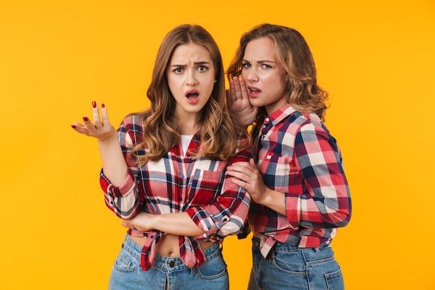 Dwie młode, piękne dziewczyny noszące koszulę w kratę, marszczące brwi i wyrażające oburzenie na białym tle