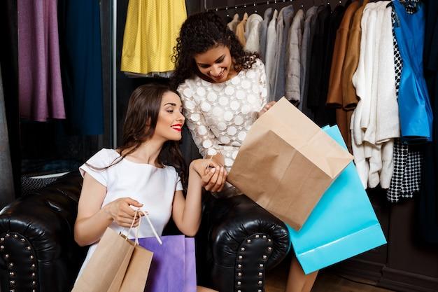 Dwie młode piękne dziewczyny ogląda zakupy w centrum handlowym.