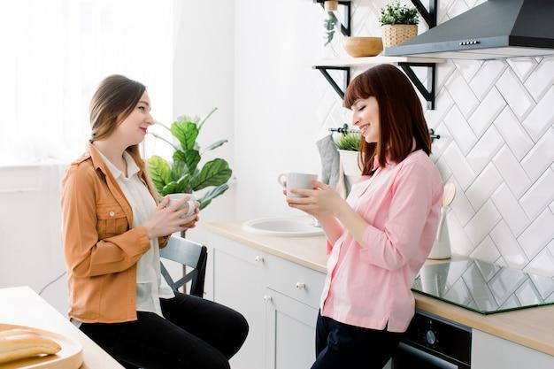 Dwie młode piękne dziewczyny piją herbatę i rozmawiają w kuchni w domu