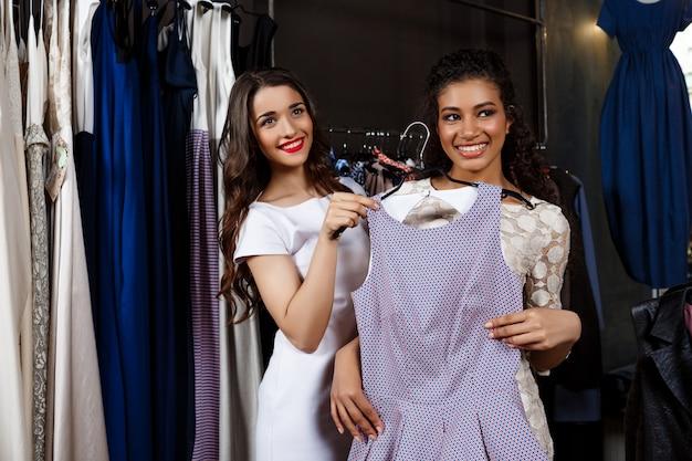 Dwie młode piękne dziewczyny robi zakupy w centrum handlowym.