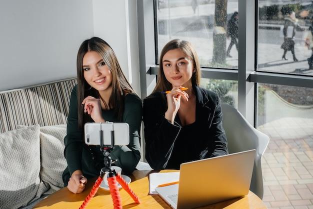 Dwie młode piękne dziewczyny siedzą w kawiarni, nagrywają wideoblogi i komunikują się na portalach społecznościowych.