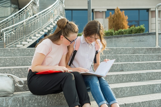 Dwie młode piękne dziewczyny uczennice z plecakami, książki