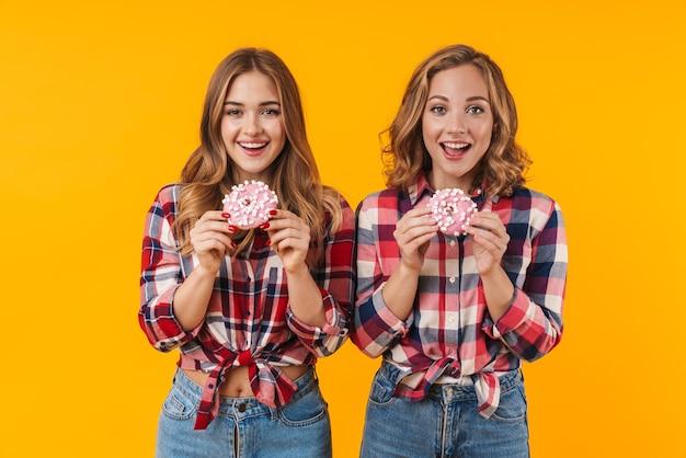 Dwie młode, piękne dziewczyny w koszulach w kratę, bawiące się i jedzące pączki na białym tle