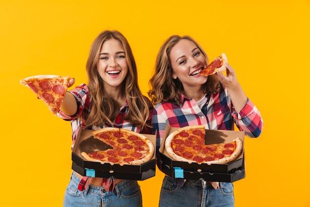 Dwie młode piękne dziewczyny w koszulach w kratę jedzące pizzę na białym tle