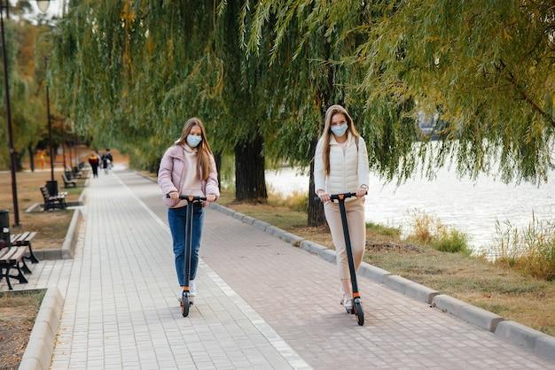 Dwie młode piękne dziewczyny w maskach jeżdżą na skuterach elektrycznych w parku w ciepły jesienny dzień. spacerować w parku.