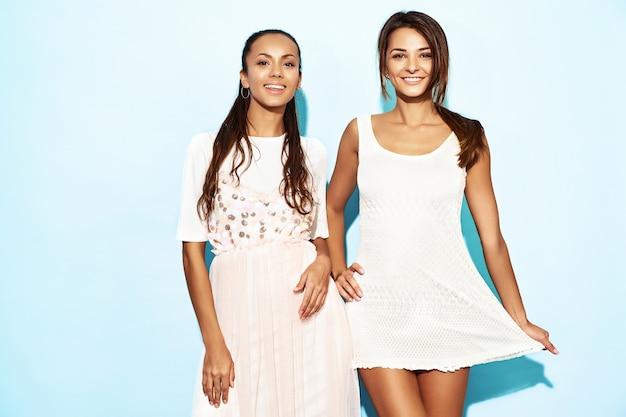 Dwie młode piękne gorące uśmiechnięte hipster kobiety w modne letnie ubrania. seksowne beztroskie kobiety pozuje blisko błękit ściany. pozytywne modele