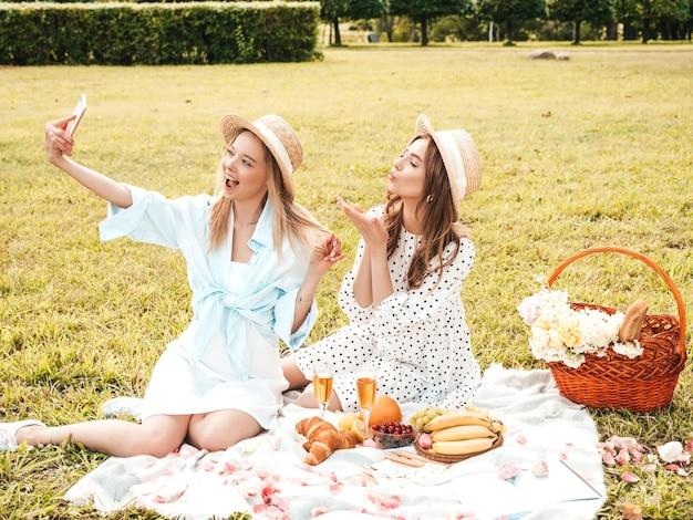 Dwie młode piękne hipster kobieta w modnej letniej sukience i kapeluszach. beztroskie kobiety robią piknik na zewnątrz.